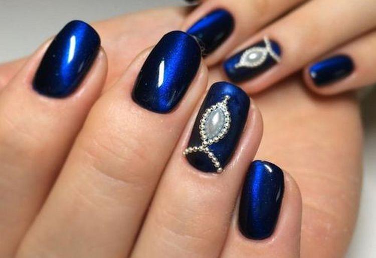 Глубокий синий цвет в маникюре органично дополнен камнем.