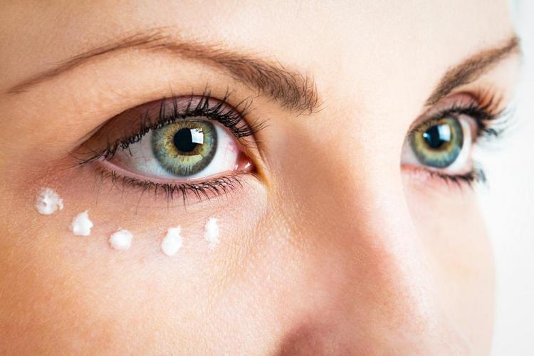 Наносим крем на кожу вокруг глаз.