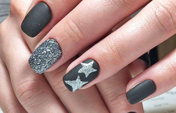Серебристые звезды на черных ногтях будут актуальными для выхода вечером.
