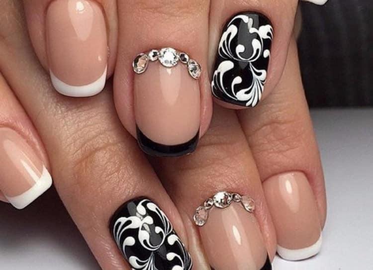 Красиво выглядят белые узоры на черных ногтях.