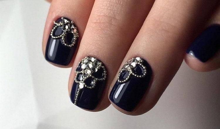 Кроткие черные ногти можно дополнительно украсить стразами.