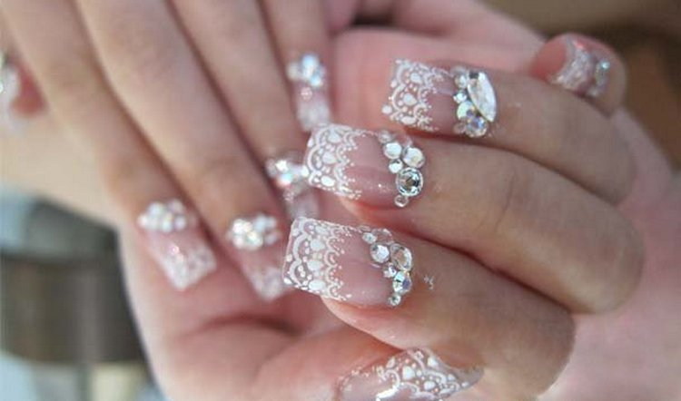 нежное белое кружево на ногтях органично дополнено стразами.
