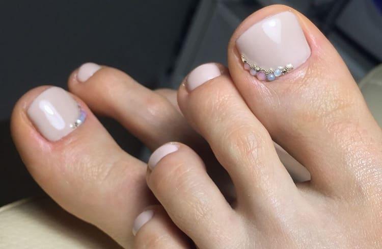 Нюдовые оттенки лака на ногах можно дополнить стразами и бульонками.