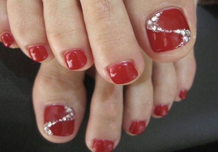Красный дизайн ногтей на ногах со стразами.