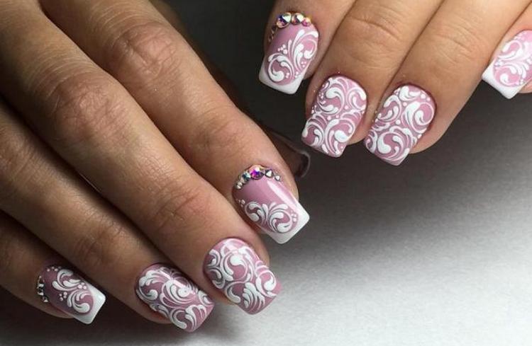Белые узоры на нежном розовом цвете ногтей выглядят очень нежно.