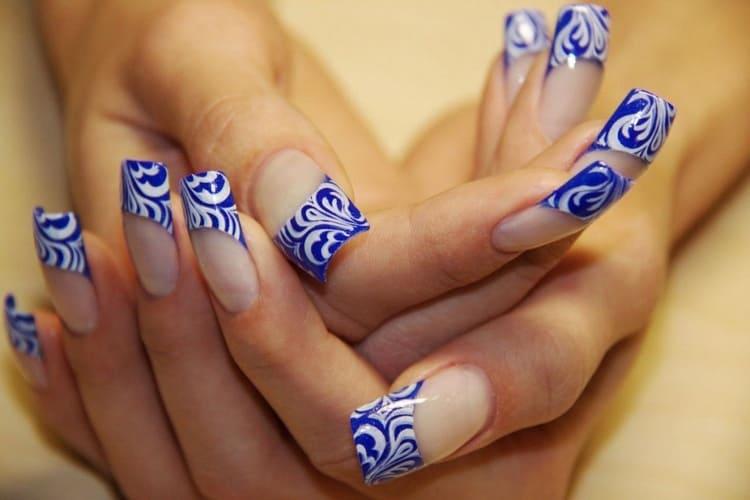 Очень стильно выглядит синий френч на ногтях с рисунком.