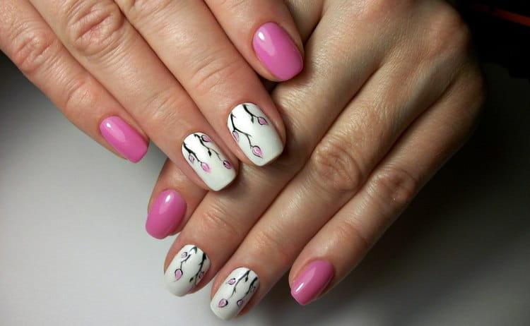 розовые цветочки на белом ногте выглядят очень нежно.