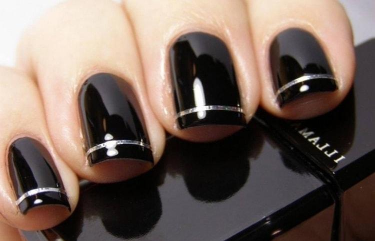 Однотонный черный маникюр можно разнообразить добавлением золотистой ленты.