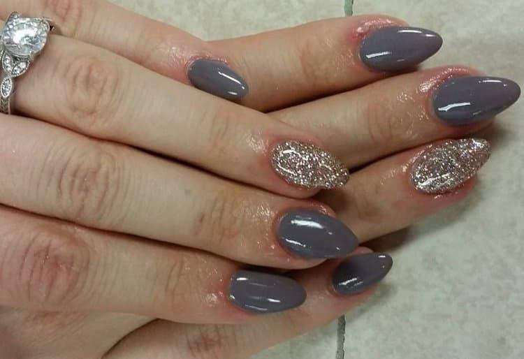 Серый дизайн ногтей с глиттером на акцентном пальце выглядит отлично.