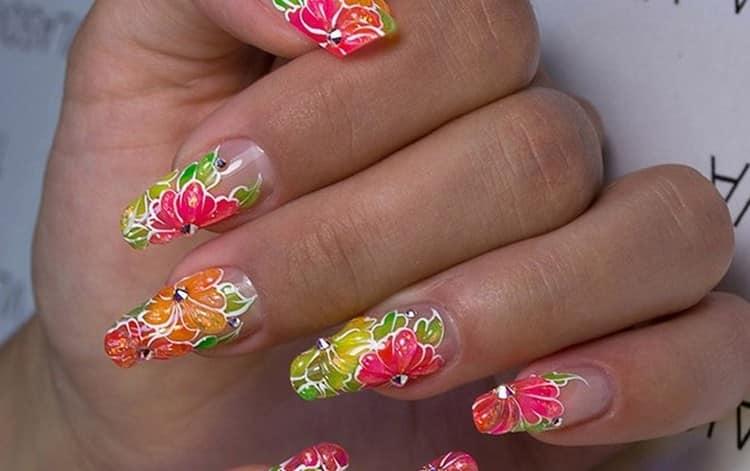 Крупные яркие цветы на ногтях дополнены стразами.