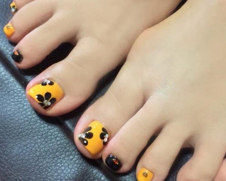 Можно сделать красивые рисунки на ногтях ног с использованием черного и желтого лака.