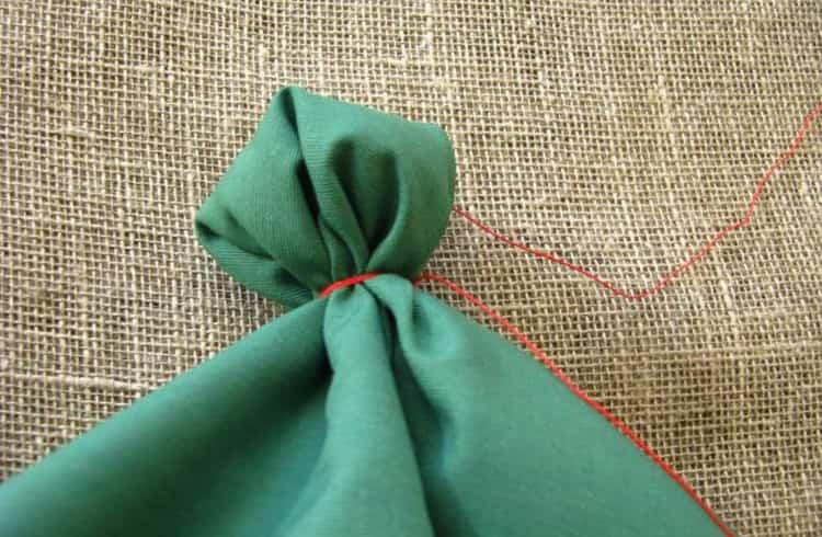 Колокольчик прячем под ткань и завязываем ее.