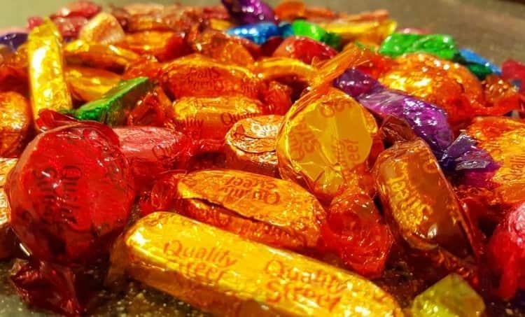 По соннику видеть много конфет в обертках это не очень хорошо.